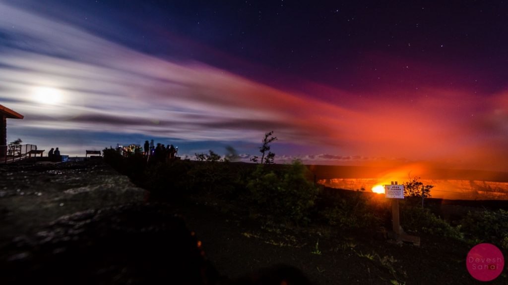 The moon shines above the burning Halemaumau Crater, and their lights meet in the middle