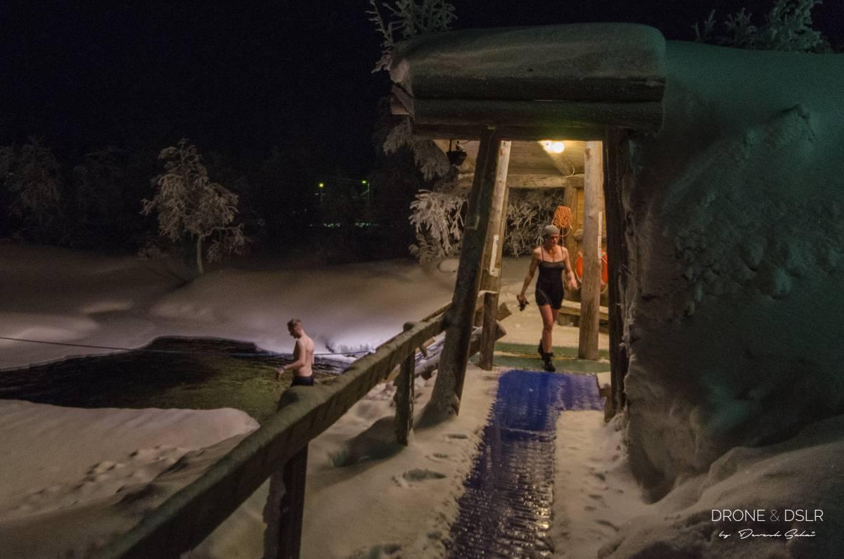 outside a tradtional Finnish smoke sauna where people take a dip in an ice lake