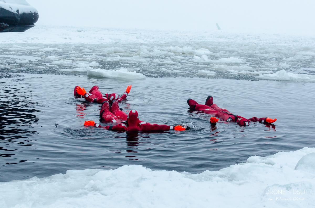 people floating in the middle of the frozen sea
